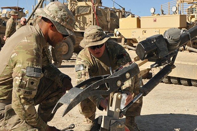 Spc. Tomas Paris, left, and Sgt. Jeffrey Maloney, both with Combined Arms Route Clearance Operation 30, A Company, 3rd Brigade Special Troops Battalion, 3rd Brigade Combat Team, 10th Mountain Division (LI), set up the mechanical claw on Maloney's vehicle at Forward Operating Base Shank, Afghanistan, before a night route clearance mission May 23. CARCO 30 is tasked with ensuring the routes used by coalition forces remain free of improvised explosive devices.