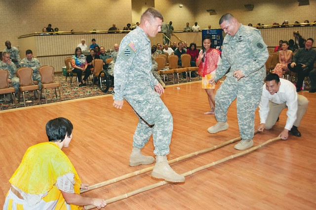 During an Asian-Pacific American Heritage Month celebration hosted by the Equal Opportunity Office staff, Sgt. 1st Class Jason Ashurst, left, 249th Engineer Battalion, and Sgt. 1st Class Jose De Haro, Northern Regional Medical Command, try to perform the tinikling dance, a popular traditional Philippine dance. Members of dance group The Culture Dancers help the Soldiers with the routine during the celebration May 29 at the Community Center.