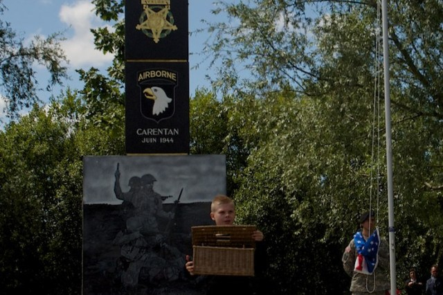 A French student releases a dove as a sign of peace at the unveiling of a new monument dedicated to Lt. Col. Robert G. Cole, June 4, 2014, in Carentan, France, as a Soldier with the 101st Airborne Division (Air Assault), stands at the flagpole. Cole posthumously received the Medal of Honor for valorous acts during the battle to free Carentan from its German occupiers.