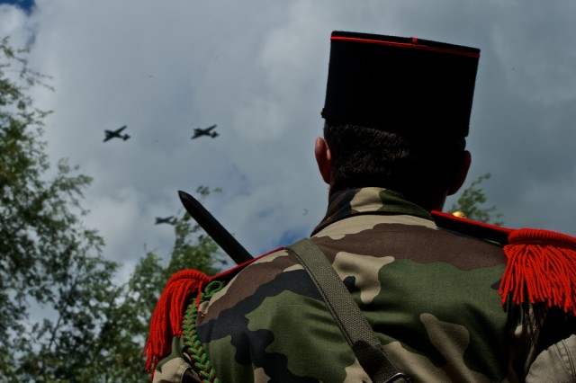 A French soldier watches the ceremonial flyover during a monument unveiling ceremony, June 4, 2014, in Carentan, France. The monument commemorates Lt. Col. Robert G. Cole, a paratrooper with the 101st Airborne Division, who posthumously received the medal of honor for valorous acts during the liberation of Carentan.