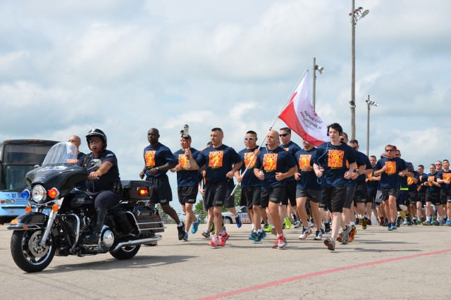 Police escort runners from the St. Robert Community Center at the start of the Law Enforcement Torch Run on May 28.