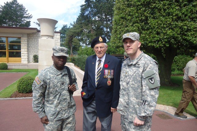 (Left) Capt. Markly Jean-Charles and Maj. Thomas Lutz (right), contingency contracting officers with the 409th Contracting Support Brigade, pose with a veteran, at the 70th anniversary D-Day commemoration, in Normandy, France.