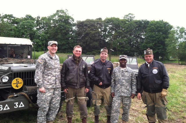Maj. Thomas Lutz (left) and Capt. Markly Jean-Charles (right), contingency contracting officers with the 409th Contracting Support Brigade, pose with actors playing the part of Allied troops at the 70th anniversary commemoration of D-Day, in Normandy, France.