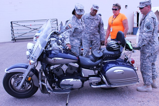 From left, Sgt. Maj. Aurora Patterson, Sgt. Maj. Tony Pomerlee, Jane Gallant and Sgt. Isreal Alday, Network Enterprise Technology Command, gather around a motorcycle on display at the motorcycle safety tent set up outside Barnes Field House for the Summer Safety Awareness Expo, which took place May 29 -- 30. Other outdoor activities included a drunk driving simulation course presented by the Army Substance Abuse Program.