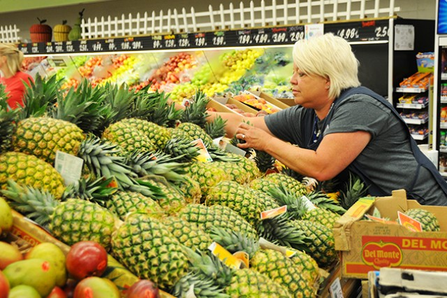 Brenda Fitts, Fort Rucker Commissary produce manager, restocks pineapples in the commissary's produce section May 30.