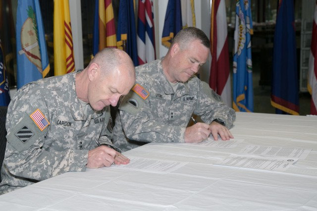 Lt. Gen. Edward C. Cardon, left, commanding general, Army Cyber Command and 2nd Army, and Maj. Gen. Judd H. Lyons, acting director, Army National Guard, sign a memorandum of understanding June 5 at Fort Belvoir, Va. that integrates an Army National Guard cyber protection team with Army Cyber Command.   (Photo by Jocelyn Broussard)
