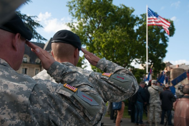 Soldiers of the 1st Infantry Division render a hand salute during a wreath-laying ceremony June 4, 2014, at the Carentan Liberation Memorial in Carentan, France. While marching in a parade, the formation stopped to pay their respects, after helping liberate the city 70 years ago. The parade and ceremonies were part of several events that took place within the city commemorating the 70th anniversary of D-Day.