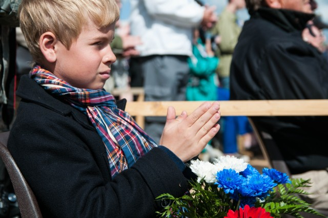 A French boy claps during a June 4, 2014, ceremony in Carentan, France. The ceremony helped dedicate a new memorial to the 101st Airborne Division, honoring those who sacrificed their lives helping liberate the city, in 1944. The boy laid flowers on the memorial during the service. There will be more than 40 ceremonies throughout Normandy during the commemorative 70th anniversary of D-Day.