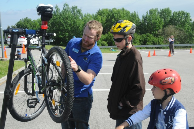 """Outdoor Recreation's Dan Ives (left) demonstrates bicycle safety checks and routine maintenance for participants at the Girl Scouts """"Bike Rodeo,"""" at Hohenfels, recently."""