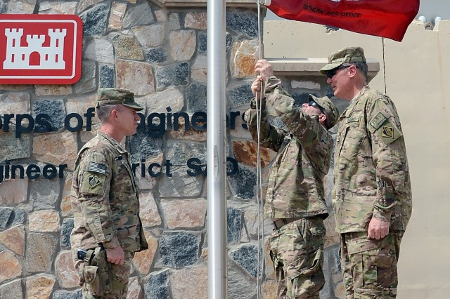 Sgt. 1st Class Harry Georgeakakais, Kandahar Resident Office non-commissioned officer-in-charge, lowers the U.S. Army Corps of Engineers South Area Office flag as  Lt. Col. John Connor South Area Office Officer in Charge, left, and KRO Officer in Charge Maj. Robert Moore ready to fold it during an inactivation ceremony June 6, 2014 at Kandahar Airfield. The Corps closed another chapter in Afghanistan as the Transatlantic Afghanistan completes projects for Afghanistan National Security Forces.