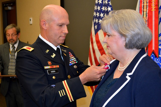 Col. Jeffrey Ogden, deputy chief of staff, engineer, U.S. Army Space and Missile Defense Command/Army Forces Strategic Command, pins the Superior Civilian Service Award on Patsy Gasser, SMDC facilities manager, during her retirmement at the command's Redstone Arsenal, Ala., headquarters May 28. Gasser retires with 22 years of service.