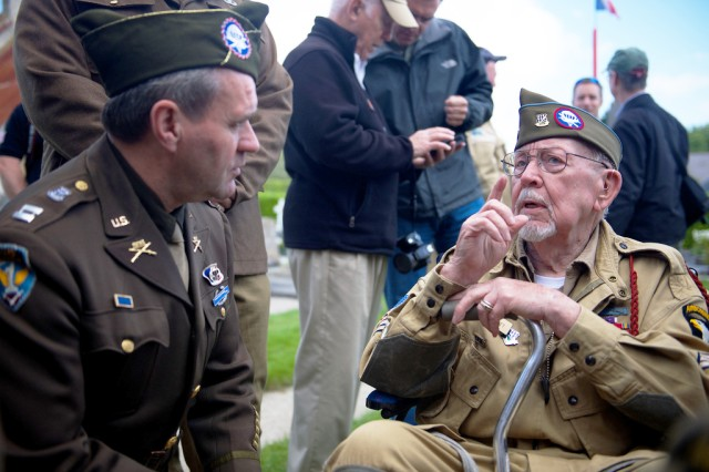 "Donald R. Burgett shares stories of the 506th Parachute Infantry Regiment, 101st Airborne Division, with a period re-enactor June 5, 2014, in Saint-Côme-Du-Mont, France, on the occasion of a memorial ceremony in honor of Joseph ""Jumpin' Joe"" Beyrle. Burgett is a writer and fellow D-Day veteran of Beyrle's unit."