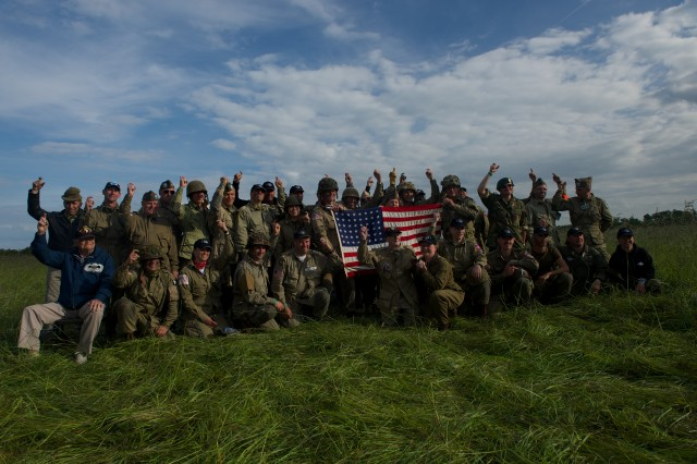 "A group of military re-enactors and parachutists join Jim ""Pee Wee"" Martin for a group photo after his historic parachute jump June 5, 2014, near Utah Beach, France. Martin returned to Normandy for a final jump, 70 years after first making his landing during the D-Day invasion of occupied France, in 1944."