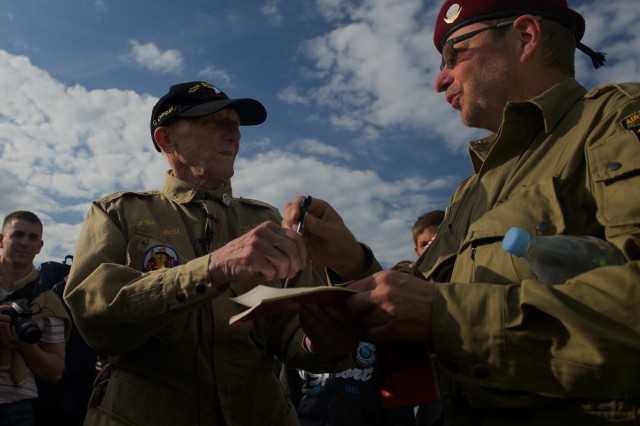 "Jim ""Pee Wee"" Martin autographs a fellow jumper's jump logbook as a souvenir June 5, 2014, near Utah Beach, France. Martin returned to Normandy for a final jump, 70 years after first making his landing during the D-Day invasion of occupied France, in 1944."