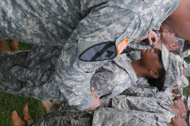 Spc. Tinita Taylor, Headquarters and Headquarters Company, 3rd Brigade Combat Team, 25th Infantry Division receives her Jungle Expert tab from Capt. Robert J. Conway, commander, C. Co., 2nd Battalion, 27th Infantry Regiment, 3rd BCT, 25th ID during a Jungle Operations Training Course graduation ceremony, here, on  June 2, 2014.