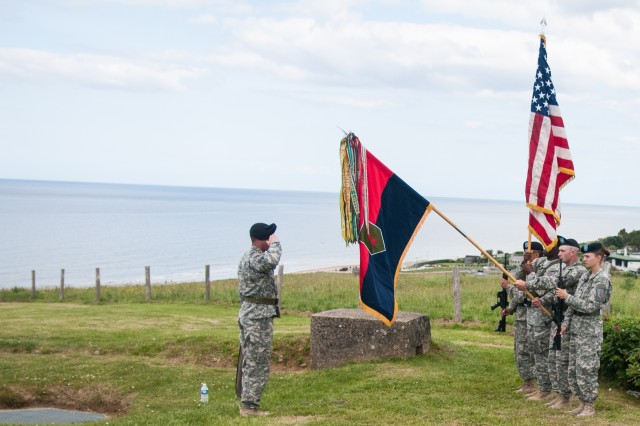 "First Sgt. Brandon McGuire, 1st Infantry Division, salutes during a colors-casing ceremony June 5, 2014, near the ""Big Red One"" monument atop Omaha Beach, in Normandy France. The Commanding General's Mounted Color Guard participated in the ceremony that honored those who died from the 1st Infantry Division during D-Day. Soldiers from multiple nations are participating in more than 40 ceremonies throughout Normandy during the 70th anniversary of D-Day."