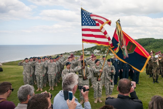 "Soldiers and the Commanding General's Mounted Color Guard, 1st Infantry Division, salute as the national anthem is played during a ceremony June 5, 2014, at Omaha Beach in Normandy, France, honoring the ""Big Red One."" The ceremony honored those from the division who died during D-Day."