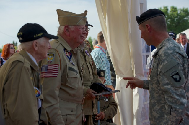"""Maj. Gen. James McConville, 101st Airborne Division (Air Assault) commander (right), congratulates D-Day veterans James """"Pee Wee"""" Martin, Bill Galbraith and Norwood W. Thomas on the occasion of their induction into the French Legion of Honor, June 6, 2014, at Saint-Côme-du-Mont, France. The World War II veterans traveled to Normandy, France, for the 70th Anniversary of their landing, in 1944."""