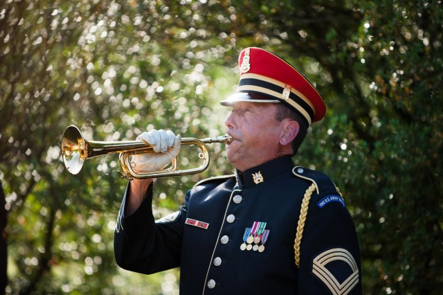 A member of the U.S. Army Band performs Taps during a ceremony to rename the Old Amphitheater in Arlington National Cemetery to the James Tanner Amphitheater May 30, 2014. Tanner, a Civil War veteran, later became a stenographer and veterans advocate after the loss of both legs during the Second Battle of Bull Run.