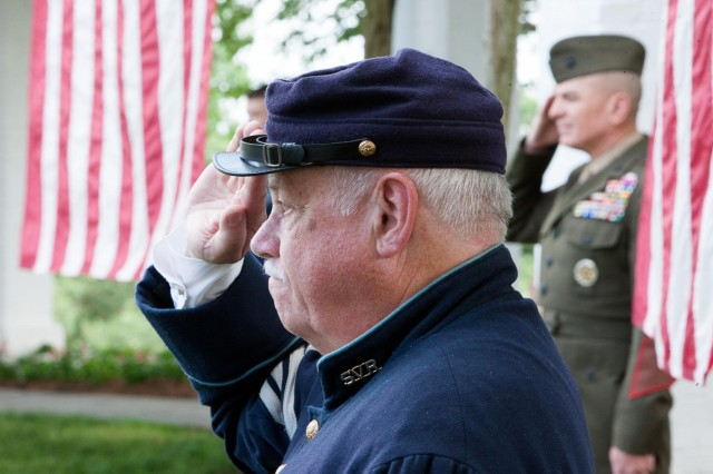 First Sgt. Lee Stone, left, with the Sons of Union Veterans Reserve, renders honors to the American flag before the start of a ceremony in Arlington National Cemetery at the Old Amphitheater May 30, 2014. During the ceremony, the Old Amphitheater was renamed the James Tanner Amphitheater.
