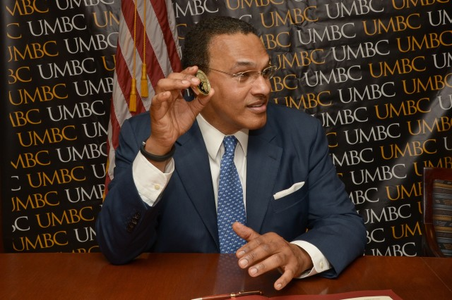 Dr. Freeman A. Hrabowski III, president of the University of Maryland Baltimore County, displays a U.S. Army Research, Development and Engineering Command director's coin following the signing of a cooperative research and development agreement June 6 in Baltimore.