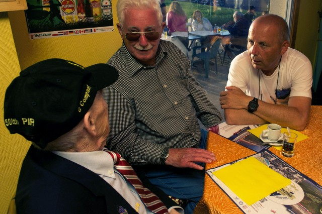 "Airborne veteran James ""Pee Wee"" Martin, left, shares his experience of his parachute landing during D-Day with Erich Bessoir, a former German Waffen-SS soldier, while amateur historian Bert Brimks translates June 7, 2014, at Omaha Beach, in Normandy, France. The veterans and former enemies, spent the evening together, exchanging experiences and memories of their fight in Normandy, in 1944."