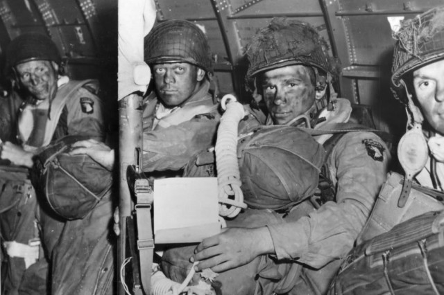 """From left, William G. Olanie, Frank D. Griffin, Robert J. Noody and Lester T. Hegland of Fox Company, 506th Parachute Infantry Regiment, 101st Airborne Division, wait for a C-47 to take off on the eve of D-Day June 5, 1944. They would be transported to Normandy by the 439th Troop Carrier Group at the end of serial No. 12 for a 0120 jump on DZ """"C,"""" Hiesville. As of August 2011 Bob Noody remains healthy and active. He lives in upstate New York with his wife of 60 years, Liz."""
