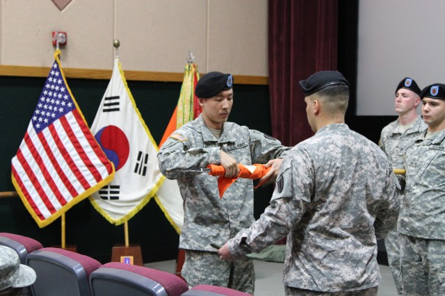 Capt. Jackson Lee, commander, 251st Signal Detachment, and Sgt. 1st Class Hiram J. Rodriguez, detachment first sergeant, roll the guidon up to prepare for the encasing at the deactivation ceremony at the USAG Yongsan multi-purpose training theater facility June 6, 2014. For nearly 12 years, the detachment has been a solid and dependable communications staple across the entire Korean Peninsula.