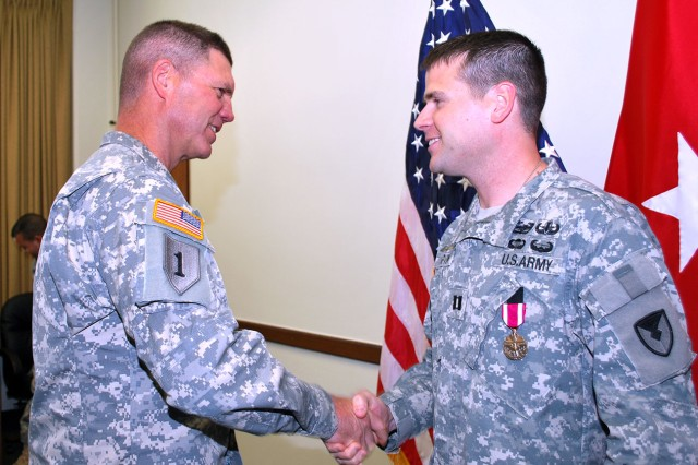 Brig. Gen. Daniel Mitchell, Army Sustainment Command deputy commanding general, congratulates Capt. Daniel Marvin after presenting him with the Meritorious Service Medal during a ceremony at the ASC headquarters building at Rock Island Arsenal, Ill., June 6. Marvin, who served as Mitchell's aide-de-camp from August 2013 to present, was accompanied by his wife, Penny. The couple will move to Fort Lee, Va., where Marvin will attend the Captains Career Course. (Photo by Dawn Marie Barnett, ASC Public Affairs)