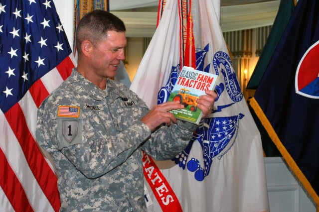 Brig. Gen. Daniel Mitchell, Army Sustainment Command deputy commanding general, reacts to a book about tractors presented by Melanie Johnson, executive director of the Army Contracting Command -- Rock Island, Rock Island Arsenal, Ill., during a luncheon in his honor at the Rock Island Arsenal Golf Clubhouse, June 6. He reminisced about his boyhood days on the farm with his father in Peoria, Ill. Mitchell's next assignment will be deputy commanding general, 1st Theater Sustainment Command in Kuwait. (Photo by Dawn Marie Barnett, ASC Public Affairs)