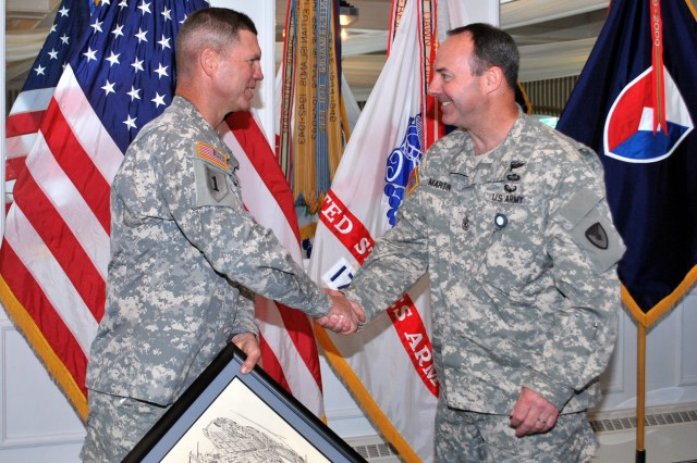 Brig. Gen. Daniel Mitchell, Army Sustainment Command deputy commanding general, and his operations sergeant major, Sgt. Maj. Douglas Martin, share a moment of mutual respect after Martin presents an artist's rendering of Rock Island Arsenal, Ill., to Mitchell at a luncheon in honor of his service at ASC. The event was held at the Rock Island Arsenal Golf Clubhouse, June 6.  Mitchell's next assignment will be deputy commanding general, 1st Theater Sustainment Command in Kuwait. (Photo by Dawn Marie Barnett, ASC Public Affairs)
