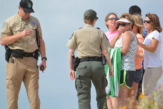 Texas Parks and Wildlife Department Game Warden Douglas Volcik, left, and members of Bosque County and Hill County Sheriffs Offices gather information from witnesses on the scene of a mock drowning. Participants wore microphones so that students from Whitney Middle School could hear what was happening during the simulated rescue and recovery operation at Walling Bend Park on Whitney Lake.