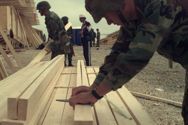 Pvt. William Helton measures and marks wood for the construction of a SEAHUT at Camp Bondsteel, Kosovo, Oct. 5, 1999. Pvt. Helton is from B Company, 94th Engineer Battalion from Vilseck, Germany. The SEAHUTs are being constructed in replacement of the General Purpose Tents at Camp Bondsteel. They will be used for housing and work spaces. The soldiers are in Kosovo in support of the peace-keeping mission NATO Opertion Joint Guardian.