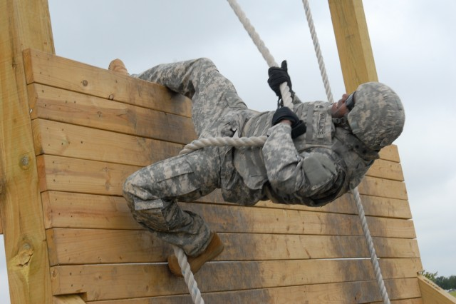 Sgt. 1st Class Joey Wallace, 3rd Battalion, 393rd Field Artillery, 479th Field Artillery Brigade, negotiates the Rope Wall Climb Challenge, part of the obstacle course at the end of the 2nd Warrior Artillery Fitness Challenge that took place recently near Division West headquarters on Fort Hood, Texas.  (Photo by Capt. Javita Facion, 479th Field Artillery Brigade, Division West Public Affairs)