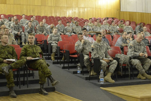 Military members from several nations gather for an Observer Coach Trainer (OCT) briefing at Adazi training area in preparation for exercise Saber Strike on June 9, 2014.   The briefing encouraged the OCTs to have the mindset of being teachers more so than controllers during the training that will take place throughout the exercise. Saber Strike is a multilateral, multifaceted exercise designed to enhance joint and combined interoperability with the U.S. and allied partners.