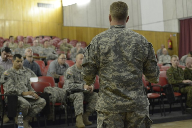 Military members from several nations gather for an Observer Coach Trainer (OCT) briefing at Adazi Training Area in preparation for exercise Saber Strike on June 9, 2014.   During the briefing Maj. Joseph Lane, Joint Multinational Readiness Center (Germany), encouraged the OCTs to have the mindset of being teachers more so than controllers. Saber Strike is a multilateral, multifaceted exercise designed to enhance joint and combined interoperability with the U.S. and allied partners.
