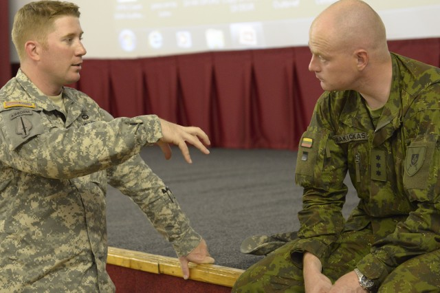 Maj. Joseph Lane with the Joint Multinational Readiness Center (Germany) discusses Observer Coach Trainer (OCT) tactics with Lithuanian Army Capt. Linas Rakickas at Adazi training area in preparation for exercise Saber Strike on June 9, 2014.   The briefing encouraged the OCTs to have the mindset of being teachers more so than controllers during the training that will take place throughout the exercise. Saber Strike is a multilateral, multifaceted exercise designed to enhance joint and combined interoperability with the U.S. and allied partners.