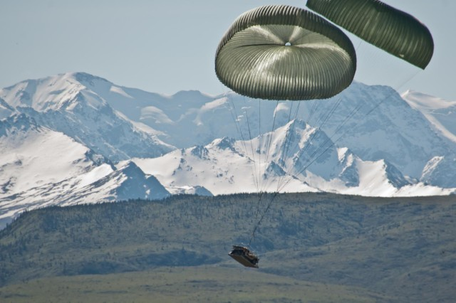 Heavy equipment dropped from an Air Force C-130 Hercules parachutes to the ground at Donnelly Training Area near Fort Greely, Alaska, June 7, 2014. The equipment was dropped for the Paratroopers of 2nd Battalion, 377th Parachute Field Artillery Regiment, 4th Infantry Brigade Combat Team (Airborne), 25th Infantry Division, to allow them to provide fires support to the paratroopers of 1st Battalion (Airborne), 501st Infantry Regiment, during a joint forcible-entry exercise to train on airfield seizure operations and wide-area security as part of the Spartan Brigade's certification as the Army's Contingency Response Force for the Pacific Theater. (Photo by U.S. Army Sgt. Eric-James Estrada)