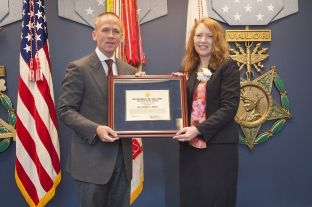 Photo Credit: Staff Sgt. Bernardo Fuller  Under Secretary of the Army Brad R. Carson presents the Nick Hoge Award to Dianne V. Smith, supervisory strategic planning specialist at Plans, Analysis and Integration Office, U.S. Army Garrison Fort A.P. Hill, Va., for using her leadership and innovation skills, coupled with her technical knowledge in building high-performing teams. The award was presented June 9, 2014, in a Pentagon Hall of Heroes ceremony.