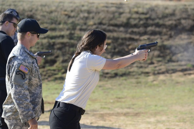 Jessica Brockmeyer, who represented the U.S. Army Public Health Command as a participant in the Executive Leadership Development Program, fires a weapon under the watchful eyes of her instructor. In addition to the academic requirements, ELDP participants had to meet stringent physical requirements.