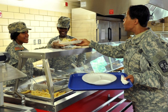 U.S. Army Reserve Spc. Coree Annis (left) and Sgt. Markeada Smith (right), both food service specialists, Task Force Wolf, serve Capt. Annette Williams, Task Force Gold, during lunch service at one of the two Soldier-operated dining facilities on Fort Knox, Ky., June 9. Seventeen Reserve Cooks, augmented by approximately 40 active duty cooks, are operating two dining facilities throughout the summer to nourish and sustain more than 11,000 Soldiers, Cadets, and cadre during Cadet Summer Training 2014. (U.S. Army photo by Staff Sgt. Shejal Pulivarti/released
