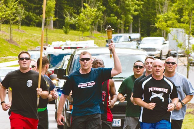 Sgt. John K. Brill, center, 212th Military Police Detachment, holds the torch high during the Virginia Law Enforcement Torch Run to benefit Special Olympics Virginia, June 5. Flanked by fellow military policemen Sgt. Stephen Hollister, left, and Sgt. 1st Class Tracy Felts, right, Brill and representatives from a number of Fort Belvoir organizations ran three miles across Fort Belvoir to hand the torch off to other law enforcement officers from the Northern Virginia area.