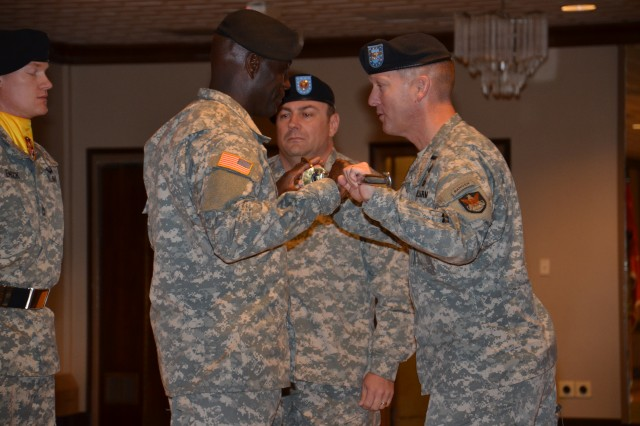 The 1st Space Brigade's new senior enlisted leader, Command Sgt. Maj. Norriel Fahie, receives the noncommissioned officer sword from Col. James Meisinger at a June 6 Change of Responsibility at the U.S. Army Space and Missile Defense Command/Army Forces Strategic Command's Peterson Air Force Base, Colo., headquarters. Outgoing Command Sgt. Maj. Thomas Eagan is at center.