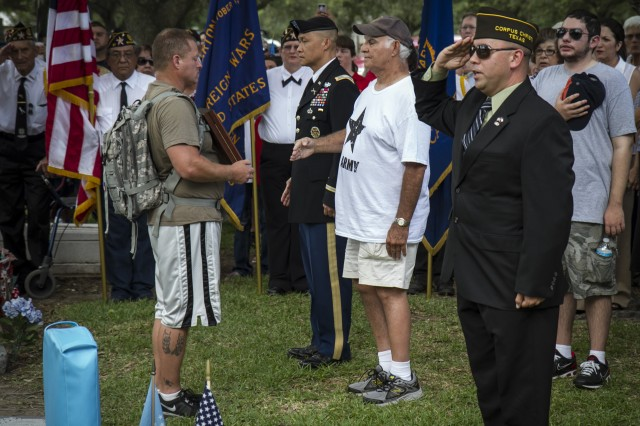 John Peña (left), grandson of Medal of Honor recipient Master Sgt. Mike C. Peña, 5th Cavalry Regiment, 1st Cavalry Division, walked 64 miles to present his grandfather's Medal of Honor to his father and Master Sgt. Peña's son, Michael (seen in white shirt), during a ceremony at the Cedarvale Cemetery in Bay City, Texas, June 8, 2014, where Master Sgt. Peña is buried.  John and three of his comrades walked 64 miles over four days to signify the 64 years since his grandfather died in the Korean War, and to signify the 64 years it took before Master Sgt. Peña was awarded the Medal of Honor.  A Medal of Honor Memorial Headstone for Master Sgt. Peña was unveiled at the cemetery.