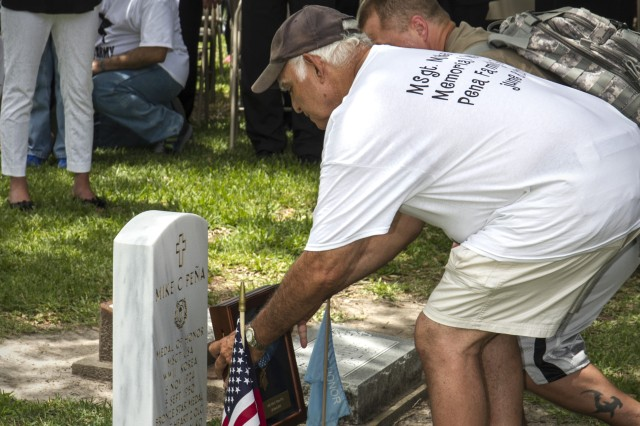 Michael Peña (left), son of Master Sgt. Mike C. Peña, 5th Cavalry Regiment, 1st Cavalry Division, and John, Michael's son and grandson to Master Sgt. Peña, place the Medal of Honor at the new Medal of Honor Memorial Headstone June 8, 2014, where Master Sgt. Peña is buried during a ceremony in Cedarvale Cemetery in Bay City, Texas.  The medal was placed there for a short time during and following the ceremony so all could see. Master Sgt. Peña was one of 24 Soldiers from World War II and the Korean and Vietnam Wars to have their Distinguished Service Cross upgraded to the Medal of Honor in a March 18, 2014, ceremony at the White House.