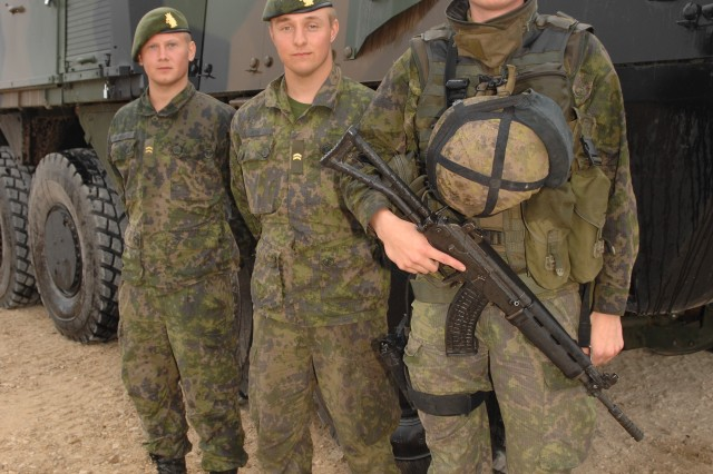 (R to L) Finnish Army Cpl. Joel Norrgard, Cpl. Jere Karho and Cpl. Aleksi Alanko display infantry equipment and an XA-360 Armored Modular Vehicle during a static equipment display event during Exercise Saber Strike 14 at Adazi, Latvia on June 12, 2014.  Saber Strike is a U.S. Joint Chiefs of Staff (JCS)-directed, U.S. European Command (USEUCOM)-scheduled, U.S. Army Europe (USAREUR)-led theater security cooperation exercise that will be conducted at locations throughout the Baltic, including the Riga and the Adazi training areas in Latvia. The exercise will consist of a host nation-supported command post exercise (CPX), a brigade-level CPX/computer assisted exercise (CAX), and a field training exercise (FTX) with a situational training exercise (STX) component. The exercise will feature the integration of U.S. close support with partner nation ground forces and a demonstration of air deployment of forces and equipment. Saber Strike 14 will be conducted June 9-20, 2014.
