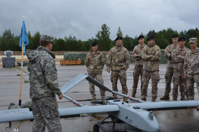 Sgt. Jonathan Gray, who flies the Shadow UAV for the Michigan National Guard unit, explains the mission and capabilities of the aircraft to Soldiers from the Latvian military at Adazi military base July 12, 2014.