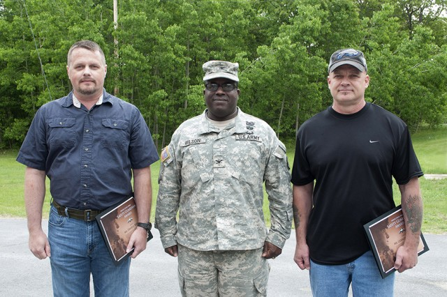 Col. David Wilson, 406th Army Field Support Brigade, Fort Bragg, N.C., congratulates David Kerley, left, and Gerald Picard, right, after presenting them with the U.S. Army Safety Guardian Award for their courageous efforts in helping a co-worker during a carbon monoxide incident late in 2013.