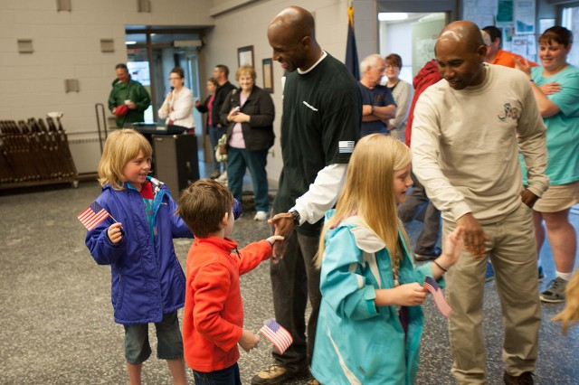 First Sgt. James L. Bryant, left, C Company first sergeant, and Command Sgt. Maj. Andre H. Saintval, right, 1st BSTB senior enlisted adviser, shake the hands of Clayton Elementary School children as they depart from a town hall building in Clayton on May 16 after serenading Soldiers who repaired their town park.