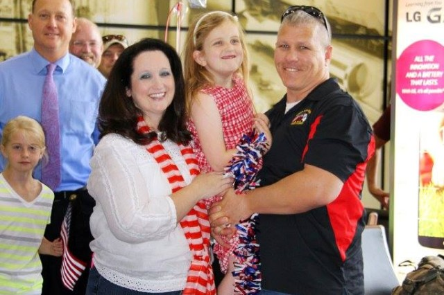 Christi and daughter Erin are joined by employees and families of SAIC at Huntsville International Airport to welcome their Soldier home for Memorial Day. Maj. Brian Moore won a free airplane ticket to visit his family through Operation Homefront. The ticket was paid for by SAIC.